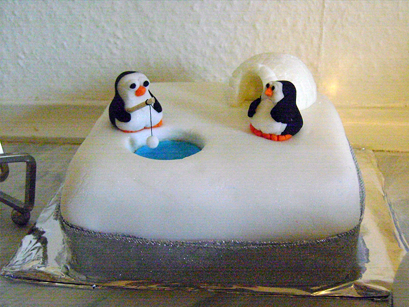 Two penguins fishing on a christmas cake