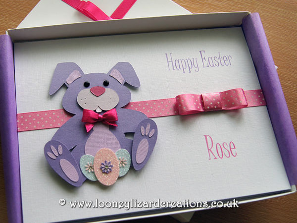 Picture of a greeting card featuring a purple rabbit with decorated Easter eggs