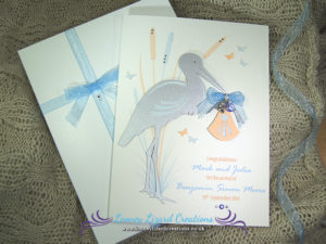 picture of a greeting card featuring a stork holding a blue baby bundle