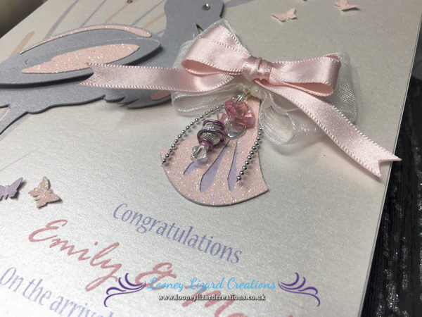 picture of a new baby card, featuring a pink bow , crystal heart & bead charm