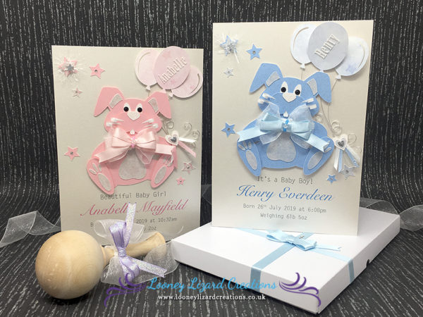 Picture of two greeting cards in pink and blue with rabbits with curly whiskers and holding balloons