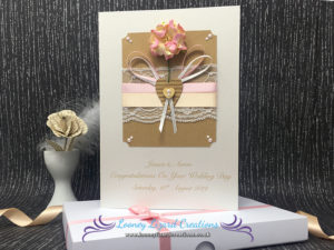 Card which features a pink flower, white lace, cabochon pearls and little wooden heart