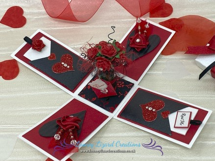 Enchanted - Features a romantic vase of half a dozen red roses with crystals centres. Including a charming little envelope with note 'To My Valentine'.