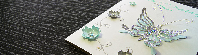 handmade card which features a butterfly and a series of paper flowers